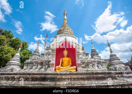 White chedi and golden Buddha statue at Wat Buppharam, Chiang Mai - Stock Photo