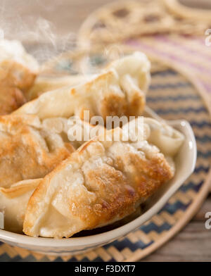 Fresh pan fried dumplings on bowl with hot steams. Asian food on rustic vintage wooden background. - Stock Photo