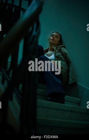 Woman sleeping on staircase - Stock Photo