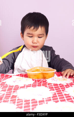 Baby feeding himself with a spoon - Stock Photo