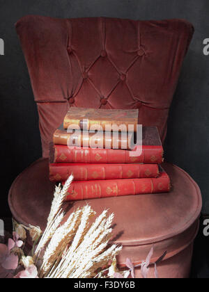Books stacked on chair - Stock Photo