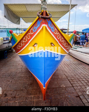 Colourful boats called Luzzus in Marsaxlokk. A luzzu is a traditional brightly coloured  fishing boat - Stock Photo