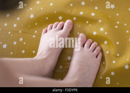 Child's feet on fabric with star pattern - Stock Photo