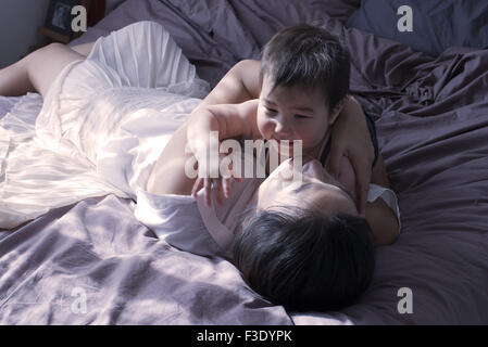 Mother and baby boy relaxing on bed together - Stock Photo