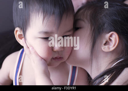 Little girl kissing baby brother on cheek - Stock Photo