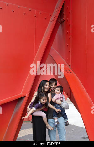 Family with two children standing beneath sculpture - Stock Photo