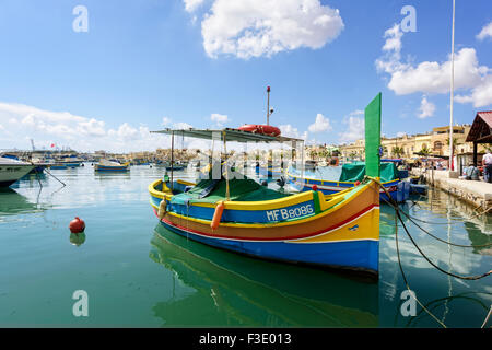 Colourful boats called Luzzus in Marsaxlokk. A luzzu is a traditional brightly coloured  fishing boat. - Stock Photo