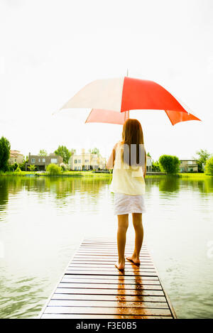Young girl standing with umbrella at end of lake pier - Stock Photo