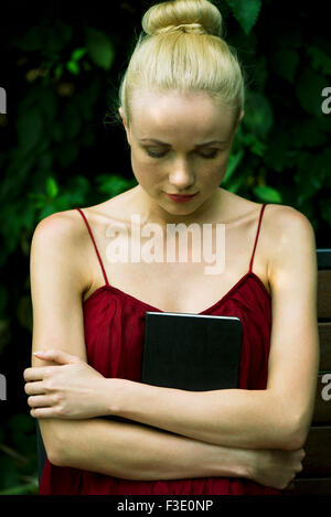 Young woman holding diary against chest, looking down - Stock Photo