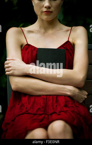 Young woman sitting with arms folded across chest, holding book protectively - Stock Photo