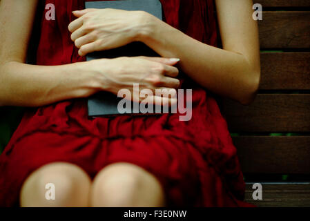 Woman sitting on bench, holding diary protectively against chest - Stock Photo