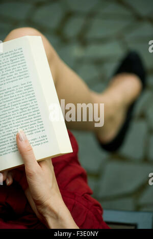 Woman reading book, over the shoulder view - Stock Photo