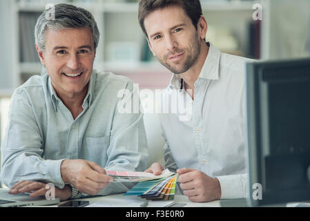 Businessmen discussing color swatches, portrait - Stock Photo