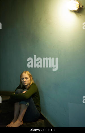 Woman sitting alone in stairwell - Stock Photo