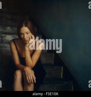 Young woman sitting alone on stairs at night - Stock Photo