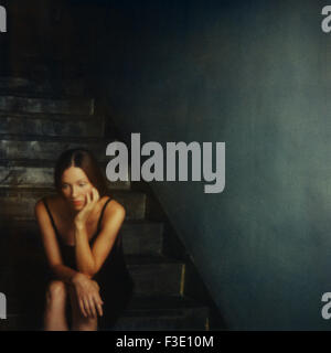 Woman sitting alone on stairs at night - Stock Photo