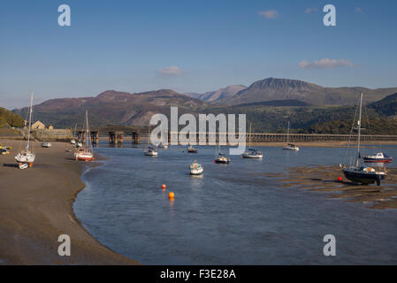 Late afternoon sun lights up a view of Barmouth harbour with old rail bridge and  Cader Idris mountain ranges in - Stock Photo