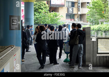 Japanese people at an outdoor smoking area in Shinagawa, Tokyo, Japan. - Stock Photo