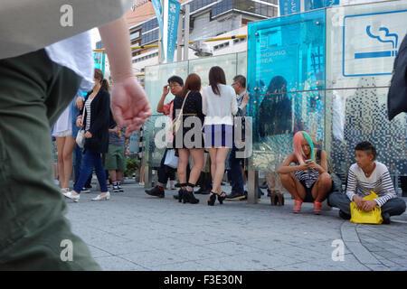 People at an outdoor smoking area in Shinjuku Ward, Tokyo, Japan. - Stock Photo