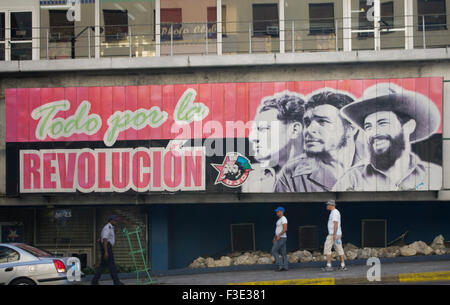 People in Havana Cuba walk past a sign translated as Everything for the Revolution, depicting Fidel Castro and two - Stock Photo