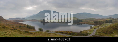 Panorama of dawn over Cregennan lakes and the distant Cader Idris mountain, Gwynedd, Snowdonia National Park, North - Stock Photo