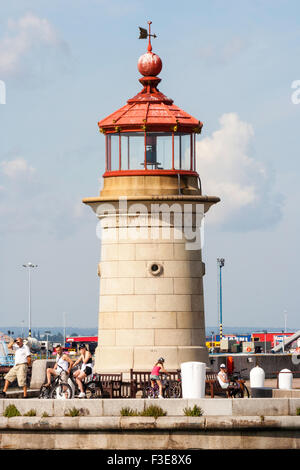England, Ramsgate Royal Harbour, small stone lighthouse at end of harbour against blue sky with scattered cloud - Stock Photo