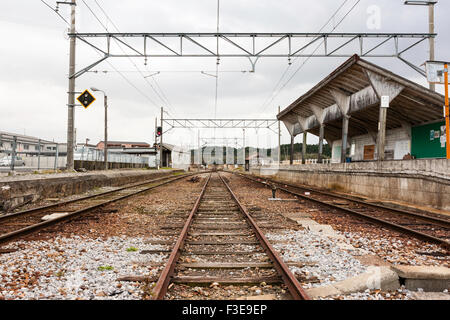 Rural station of the Ōmi Tetsudō Japanese private railway in Shiga, Japan, weathered and old under grey stormy skies - Stock Photo