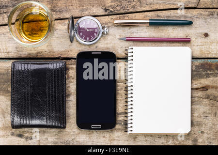 Men's mock up business set on wooden background. Wallet, smartphone, notebook  and glass of whisky top view image - Stock Photo