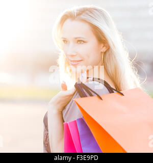 Young woman stands with shopping bags against sun. Beautiful adult girl at the outdoors after shopping - Stock Photo