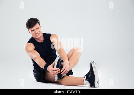 Portrait of athletic man suffering from pain in ankle isolated on a white background - Stock Photo