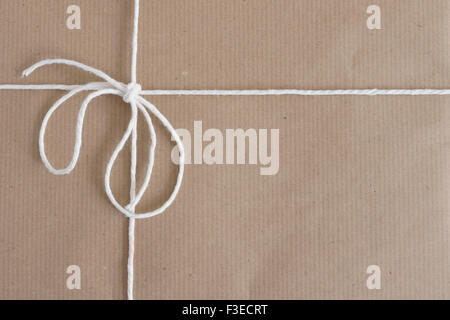 Parcel wrapped with brown paper and tied with string with copy space - Stock Photo
