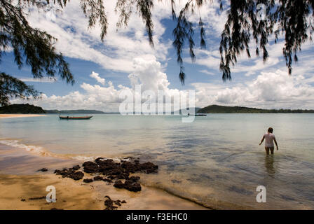 Swimming at the beach on the island of Koh Russei. Koh Russei is still living under the shadow of its former self, - Stock Photo