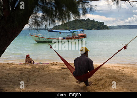 Lying in a hammock on the sea shore of the island of Koh Russei. Koh Russei (or Bamboo Island as it's commonly known) - Stock Photo
