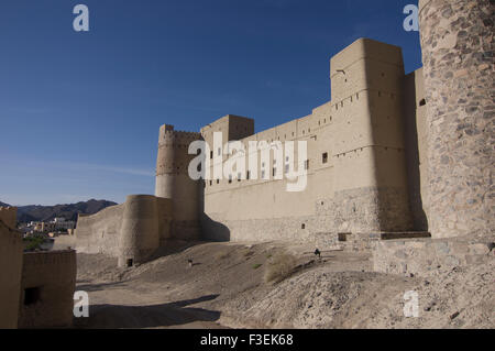 Ornate ancient adobe fortress ruins in a town in the Sultanate of Oman, a safe, friendly Gulf State holiday destination - Stock Photo