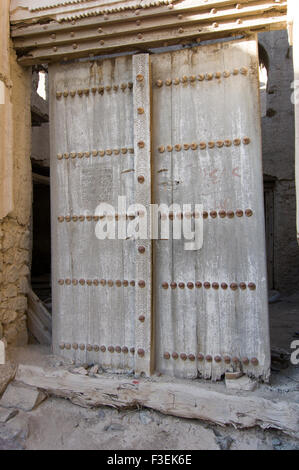 Ornate door in an ancient adobe fortress ruins in the Sultanate of Oman - Stock Photo