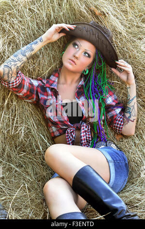 young tattooed  stylish woman with dreadlocks in cowgirl style - Stock Photo