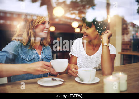 Two multi ethnic friends enjoying coffee together in a coffee shop viewed through glass with reflections as they - Stock Photo