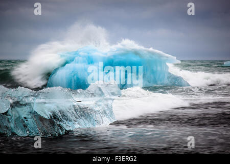 Big waves smashing against a big iceberg in the open sea, Jökulsarlon, Iceland - Stock Photo