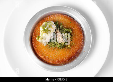 Delicious traditional Turkish dessert kunefe with pistachio powder over white background - Stock Photo
