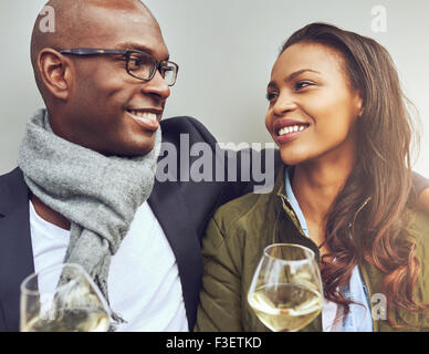 Romantic young African American couple sitting arm in arm enjoying glasses of white wine and smiling lovingly into - Stock Photo