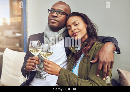 Blissful romantic young African couple relaxing in each others arms while enjoying a drink of white wine at a restaurant - Stock Photo