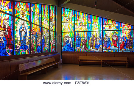 Inside details of Annunciation Catholic Church.  Colorful Stained glass windows depict scenes from the Bible for - Stock Photo