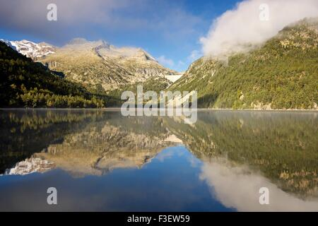 Morning mist shrowds the peaks around a still Lac D'oredon in the pyrenees - Stock Photo
