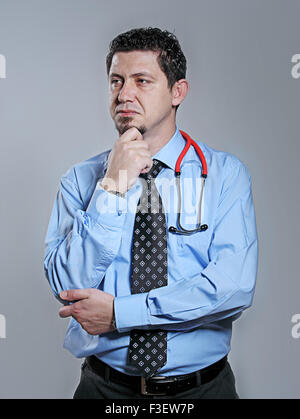 portrait of handsome thoughtful male doctor looking away - Stock Photo