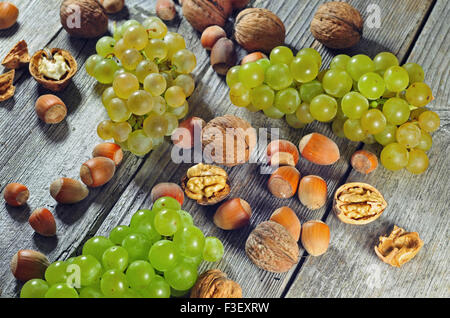 Photo of grape berries, hazelnuts and walnuts on a wooden table - Stock Photo