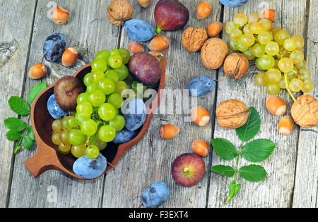 Fresh ripe autumn fruits on a wooden table - Stock Photo