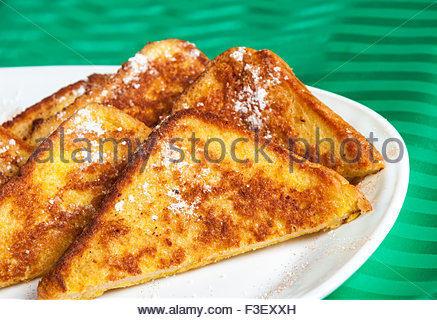 Plate of French toast.  Five slices of French toast sit on a white plate, dusted in powdered sugar.  The plate is - Stock Photo