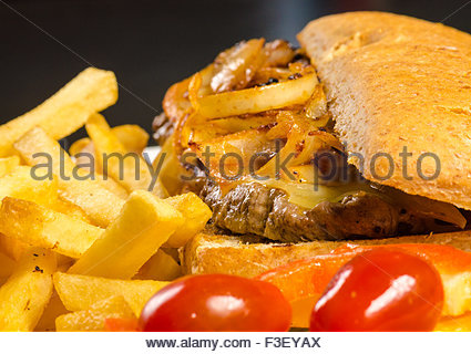 Burger and fries.  The burger is topped with caramelized onions and cheese, with a side of French fries and cherry - Stock Photo