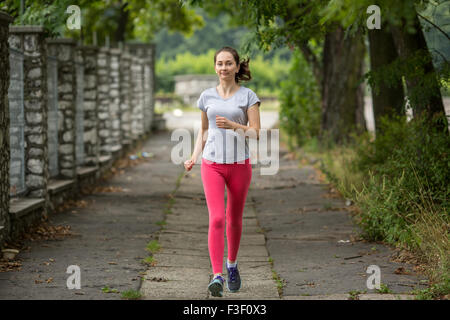 Young sports girl during a jog in the Park. Running, healthy lifestyle. - Stock Photo