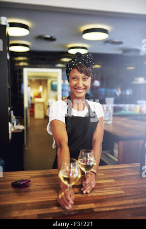 Pretty successful African American businesswoman standing behind the wooden counter in her pub serving glasses of - Stock Photo